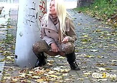 Lusty blond MILF in autumn coat pisses in the mid of the street
